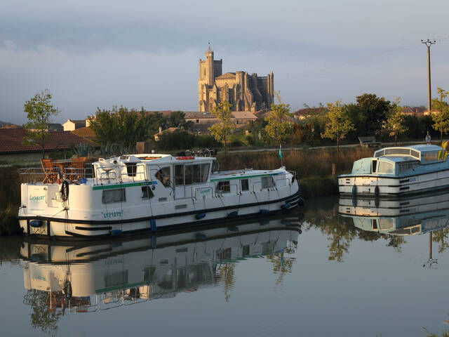 Barge on the Canal du Midi and the collegiate church of Capestang in the background © G.Souche